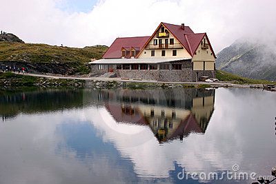 Cabin on a lake, with reflections in the water.