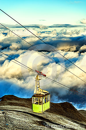 Cabina di funivia che va su alla cima della montagna sopra le nuvole