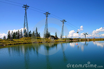 Cable car summit with blue sky and lake reflections