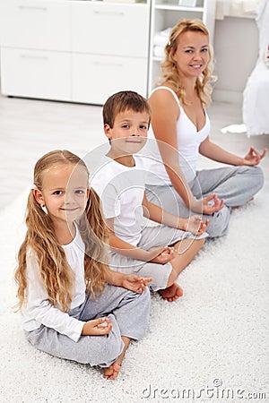 Cabritos que hacen la relajación de la yoga con su madre