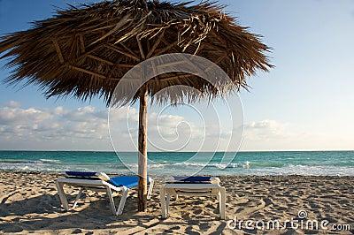 Cadeiras de praia e cabana da máscara