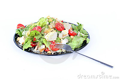 Caesar salad on black plate with fork