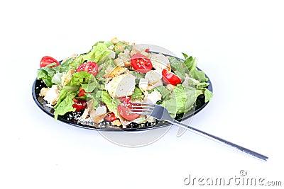 Caesar salad on black plate with fork