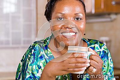 Café bebendo da mulher africana em casa