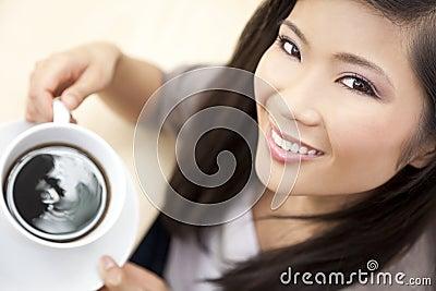 Café de consumición del té de la mujer asiática china hermosa