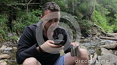Café y aplicaciones de la bebida de Guy Hikers el teléfono en acampar cerca de The Creek almacen de video