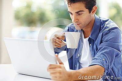 Café bebendo feliz do homem novo e utilização de um portátil