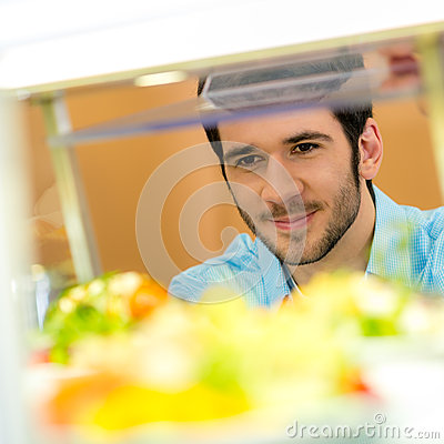 Cafeteria food display young man choose salad