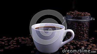Caffè e caffè Una tazza bianca di caffè sul tavolo con un fagiolo tostato Movimento lento stock footage