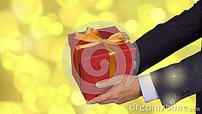 Caixa de presente vermelha de duas posses masculinas das mãos com curva do ouro Comemore a caixa de presente atual da véspera Hom filme