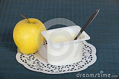 Caja con el yogur, la manzana y una servilleta