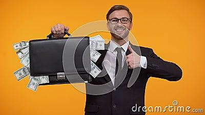 Caja de demostración del hombre llena con el dinero, guiñando y haciendo los pulgares-para arriba, préstamo, crédito almacen de video