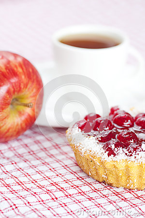 Cake with berries and tea on plaid fabric