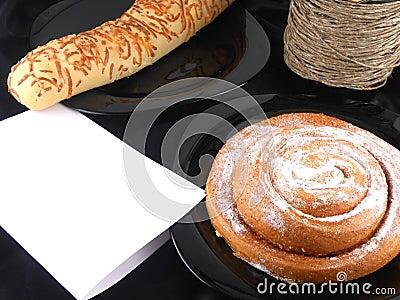 Cake on black background, white paper and wine bottle