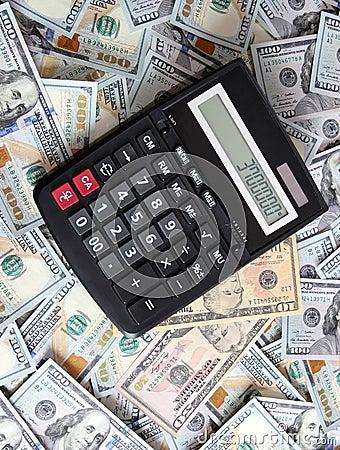 Calcolatore su un fondo di cento banconote in dollari