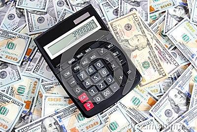 Calculadora en el fondo de cientos billetes de dólar