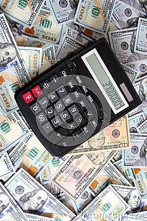 Calculadora en el fondo de cientos dólares de cuentas