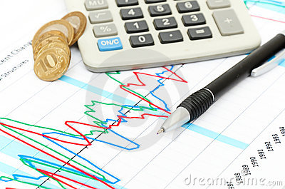 Calculator, coins and pen laying on chart.