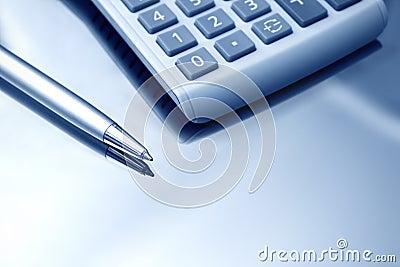 Calculator and pen. Close up.