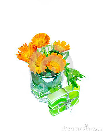 Calendula flowers in a  glass and green gift soap of  on a white
