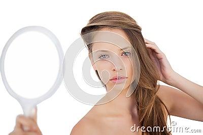 Calm brunette model posing holding a mirror