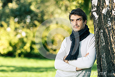 Calm man in scarf looking to side outdoors