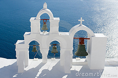 Calm sea, white church arch, bells Santorini