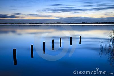 Calm sunrise over a lake with clouds reflection in