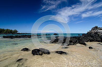 Calm waters behind black basalt rocks at  Puako beach