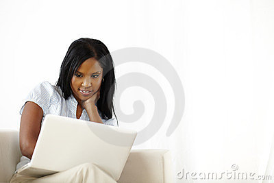 Calm young woman working on laptop at home