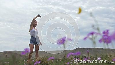 Caméra suivre une jeune femme hipster en t-shirt blanc jeans courts flottants de cheveux longs Une fille dansant sur le portable clips vidéos