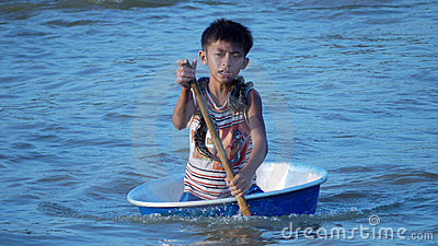 Cambodian boy (with snake) paddling in a basin Editorial Photography