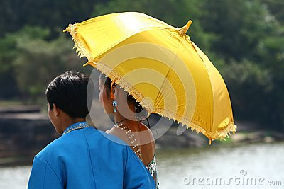Cambodian couple under yellow umbrella Editorial Stock Image