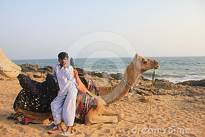 Camel and boy by the Sea Editorial Stock Image