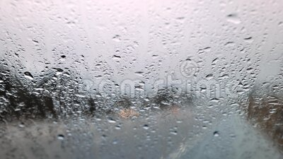 Rain water drops on the windshield in a rainy day stock footage