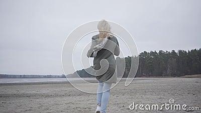 Camera naar volwassen blonde blanke vrouw in warme kleren op het strand van het najaar Joyful girl die plezier maakt ondanks stock video