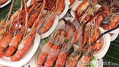 Camerabeweging van braadstuk en houtskoolgrill van gekookte zeekreeften in een plastic plaat Het is een traditioneel Thais zeevru stock footage