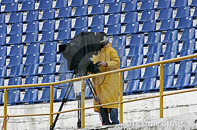 A cameraman filming a football game on a stadium