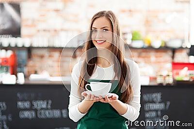 Cameriera di bar che tiene tazza di caffè