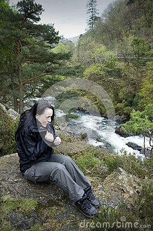 Caminante femenino cerca del frío de sensación del río
