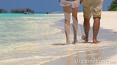 Caminhada dos pares ao longo da praia Feche acima dos pés e das ondas filme