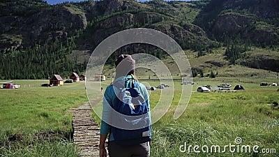 Caminhada Menina do viajante com trouxa e chapéu que anda em uma ponte nas montanhas Acampar está na distância aventura video estoque