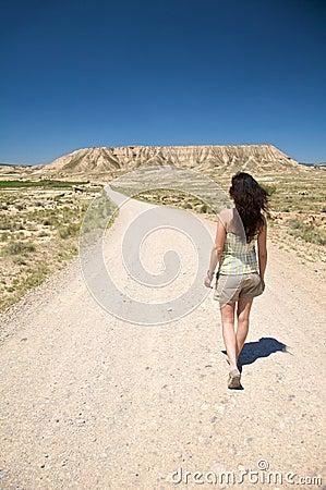Caminhando a mulher na estrada do deserto