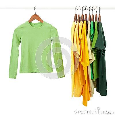 Camisas verdes e amarelas em ganchos de madeira