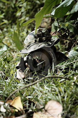 Camouflaged soldier in the bushes