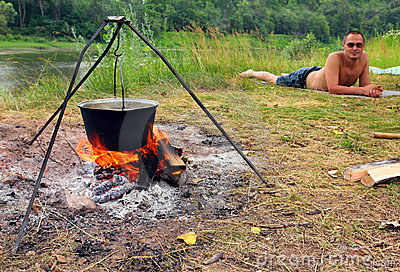Camping - kettle and lying tourist