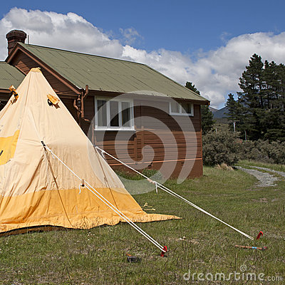 Camping tent and wooden hut in the mountains