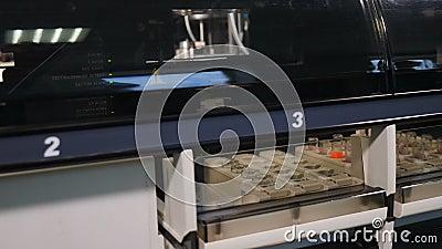 Campioni di sangue in rack in una macchina automatizzata per l'analisi del DNA umano o del sangue, concetto di apparecchiatura di archivi video