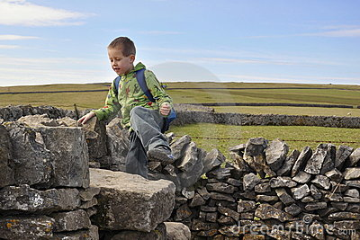 Campo inglés: muchacho que sube la pared drystone