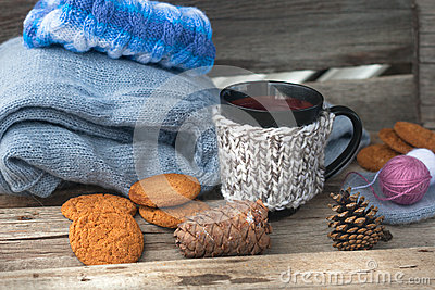 Can with hot beverage and knitting clothes